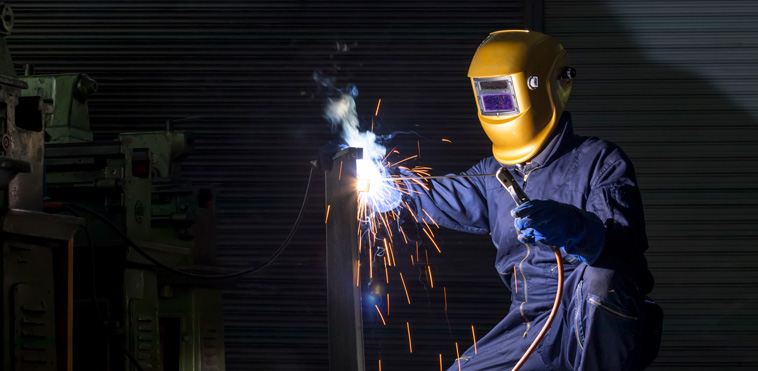 A man welding while wearing a yellow welding mask