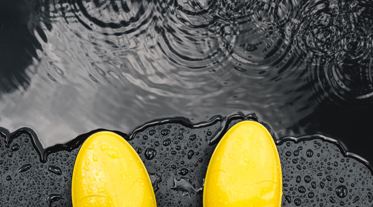 wet yellow boots next to a puddle of water
